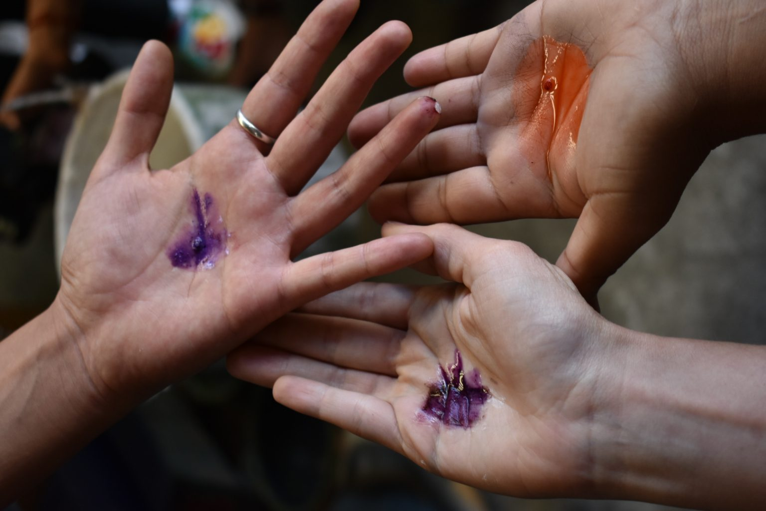 Close up of three makers' hands in a circle with natural dye colours in their palms