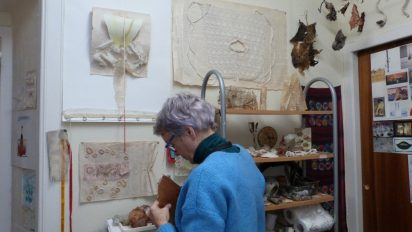 Older, female textile artist in a blue jumper in her studio, standing with her back to the camera holding an looking at a piece of her work at roughly chest height, in front of a wall with more of her works, works in progress, research, inspiration & found objects pinned to the wall, hanging from the ceiling and placed on shelves.