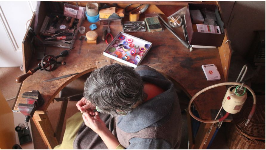 Bird's eye view of a female older jeweller working on an intricate hand process just off to the side of the wooden jewellery bench in her studio. On the surface of the bench are files of different sizes and profiles, a hand drill, various smaller hand tools that are loose and in tins, containers for liquid, plus a shallow, square white cardboard box containing brightly coloured brooches / parts of brooches 3D printed in plastic.