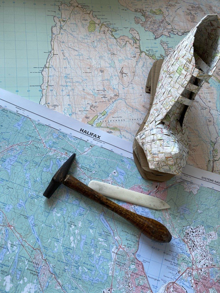 Ankle height boot made from woven map paper on a corrugated cardboard sole, alongside a small hammer and bone folder on laid out, overlapping detailed maps of the west coast of Scotland and Halifax, Canada.