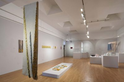 Exhibition installation of craft objects and sculptural works displayed on neutral plinths and walls