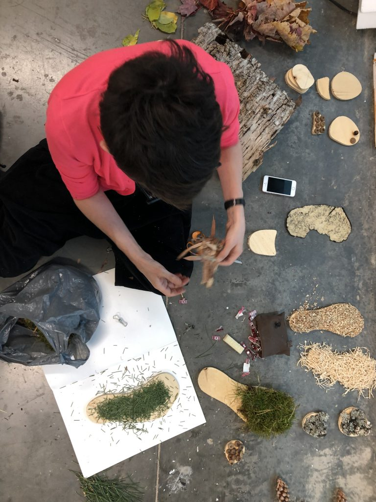 Female seated on the floor working with and composing samples of organic materials including grass, grain and wood