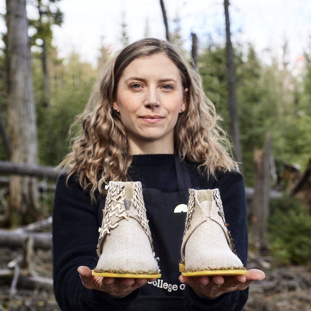 Standing female artist holding a hand made ankle height boot in a forest