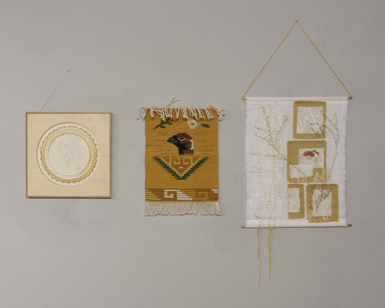 Three textile works hanging in a row on a white wall. The middle piece is woven and depicts a grouse's head on a dark yellow ground. The pieces on the left and right are stitched.