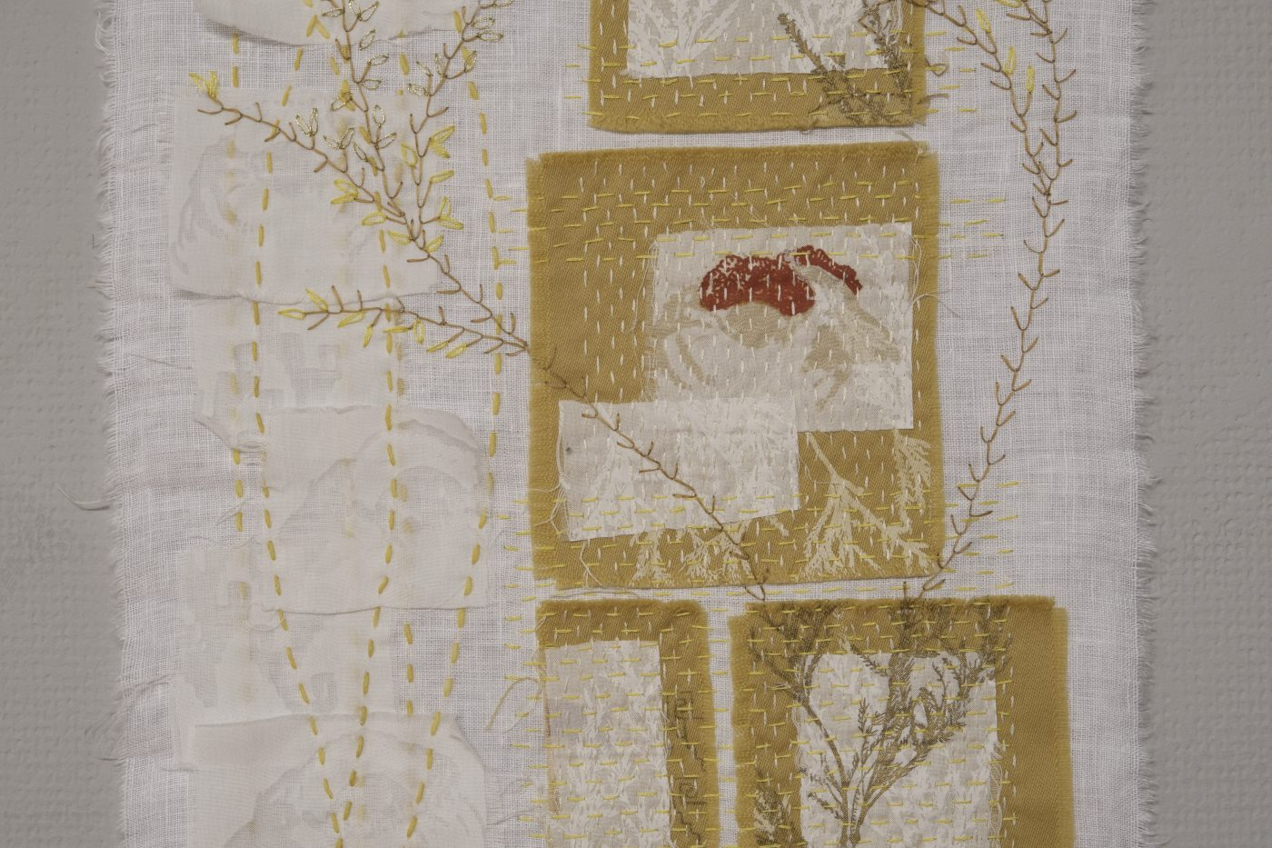 White hand stitched textile artwork with appliqued elements in dark yellow