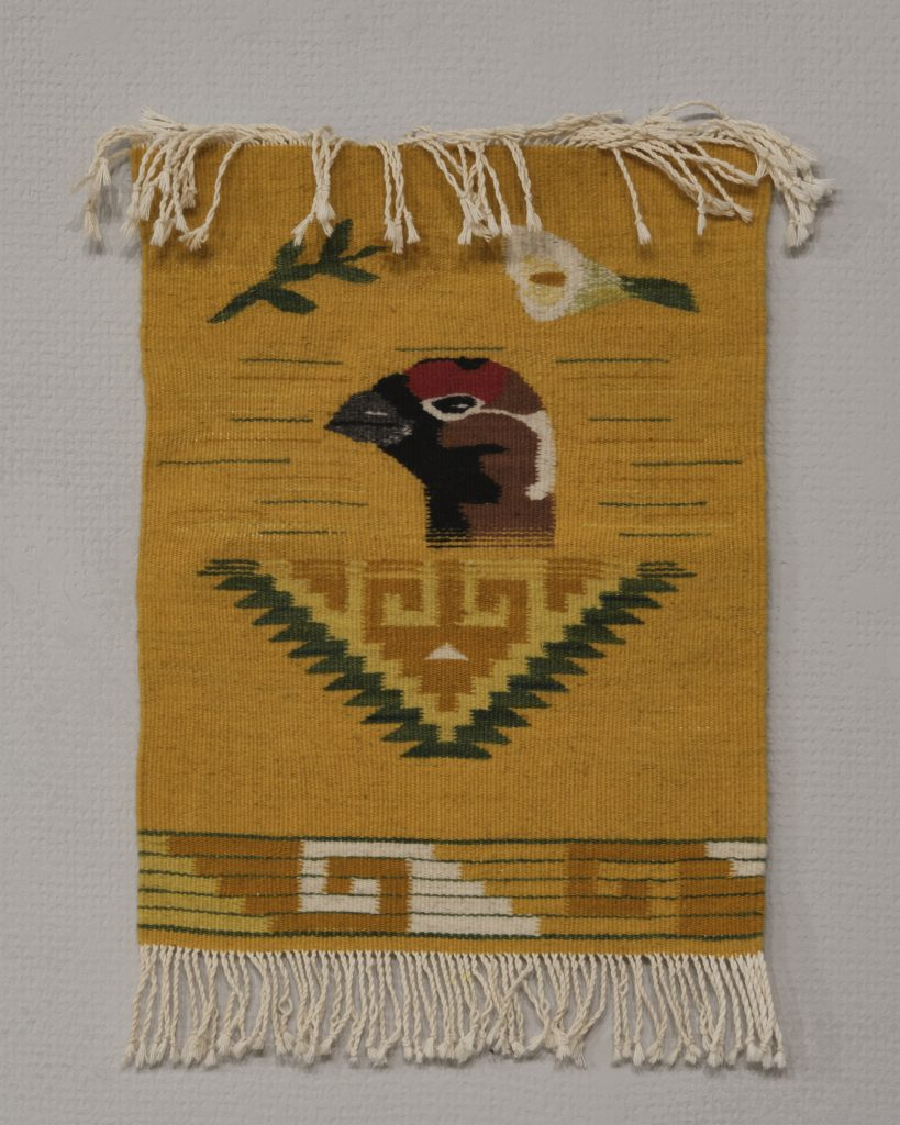 Weaving depicting a grouse's head on a dark yellow ground, with fringing top and bottom.