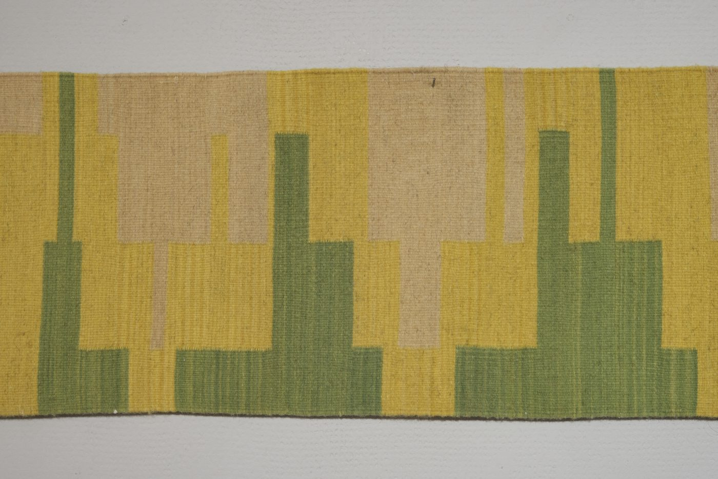 Handwoven long thin rug, with block pattern in greens, yellows and neutrals