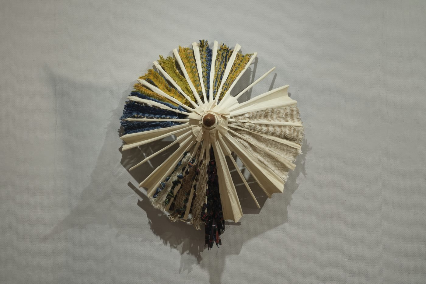 A wall-mounted open umbrella frame with handwoven yellow, neutral and blue fabrics between the sections