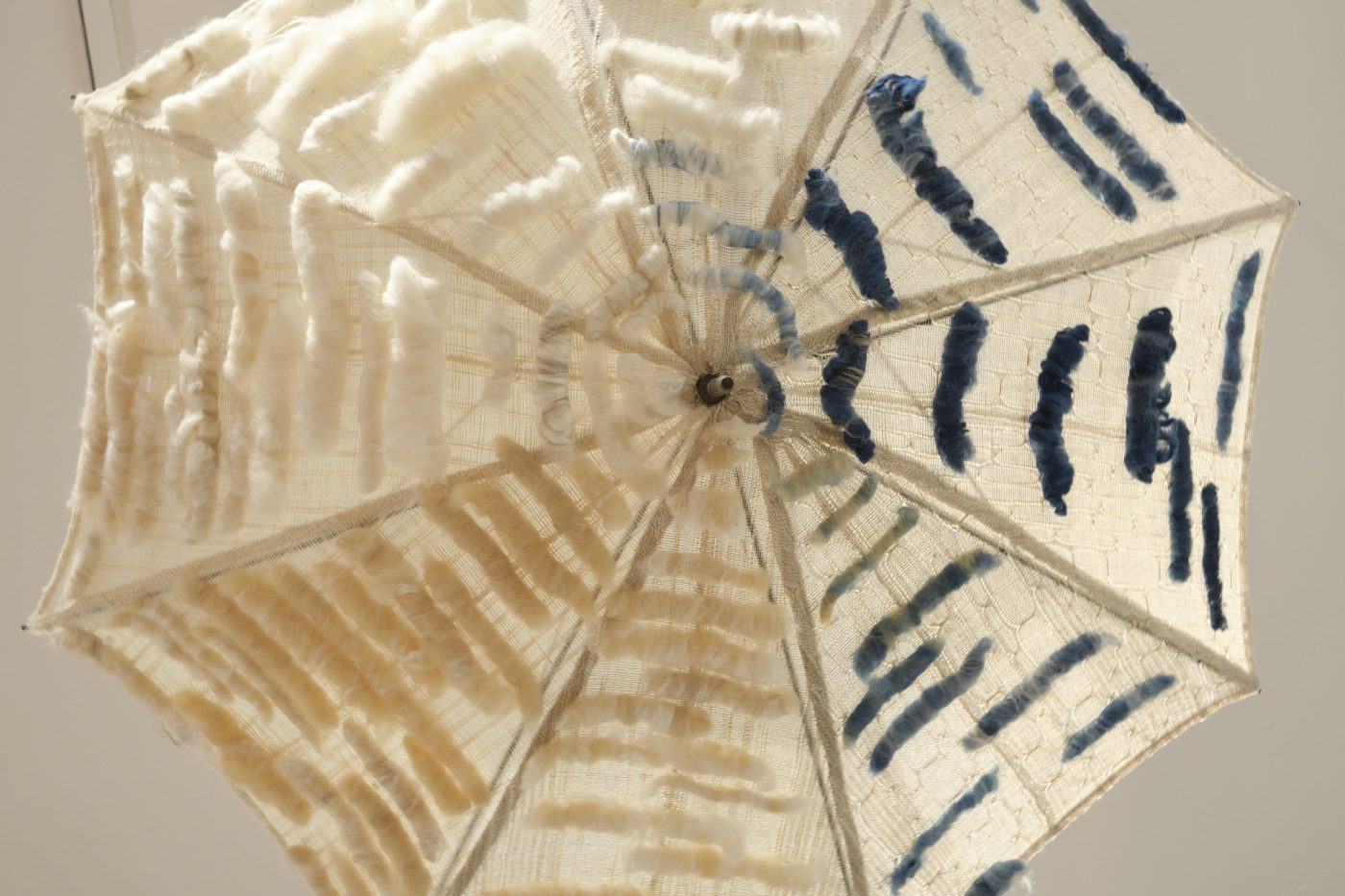 Open umbrella hung from the ceiling, covered in an open weave cream cloth with blue, yellow and cream role of fibre applied to the surface