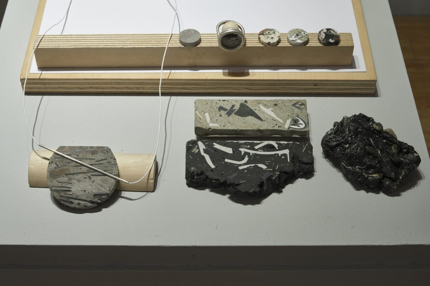 Cross sections of samples of plastic composite material, with small pieces made into rings and a necklace using silver elements