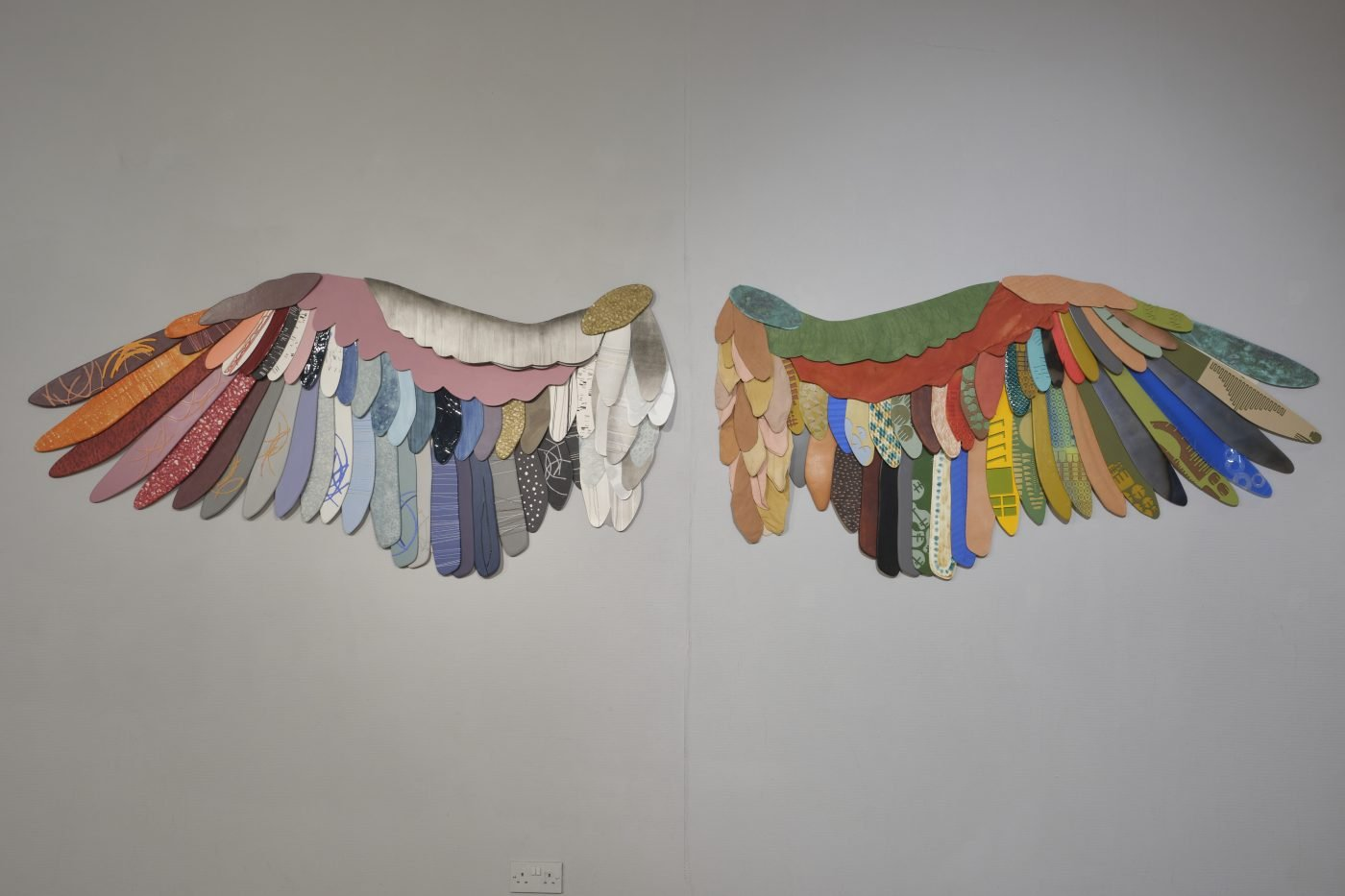 Two wall-mounted, human scale wings made from overlapping layers of varying materials cut into feather shapes