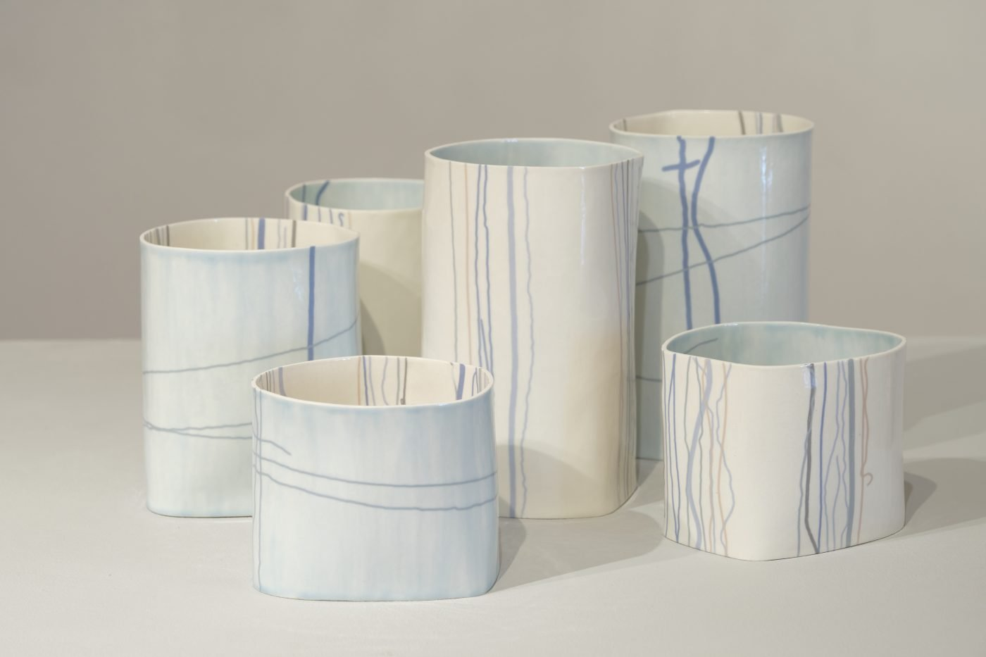 Six ceramic vessels of differing heights in neutral and blue tones with linear decoration on the inside and outside