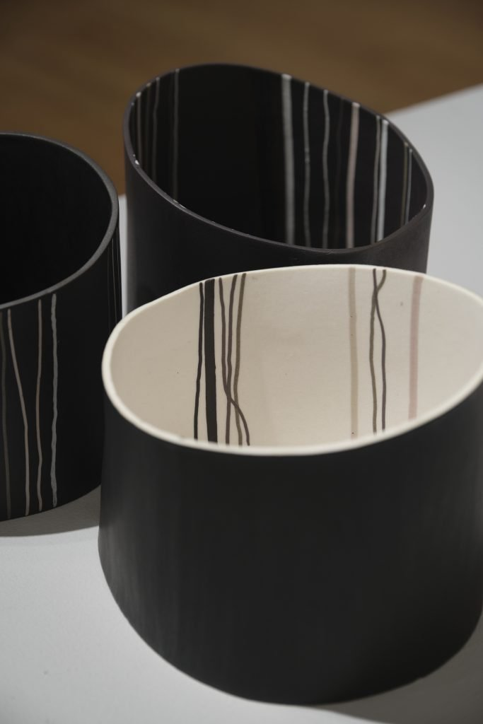 Three short black ceramic vessels with vertical linear inlaid decoration in white and grey on the inside and outside