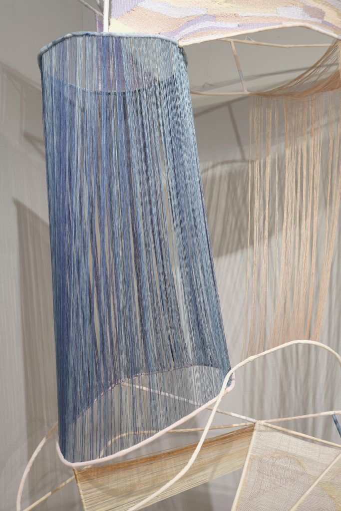 Hanging, organic metal frame with textile elements in blues, pastel and neutral colours strung and woven between elements