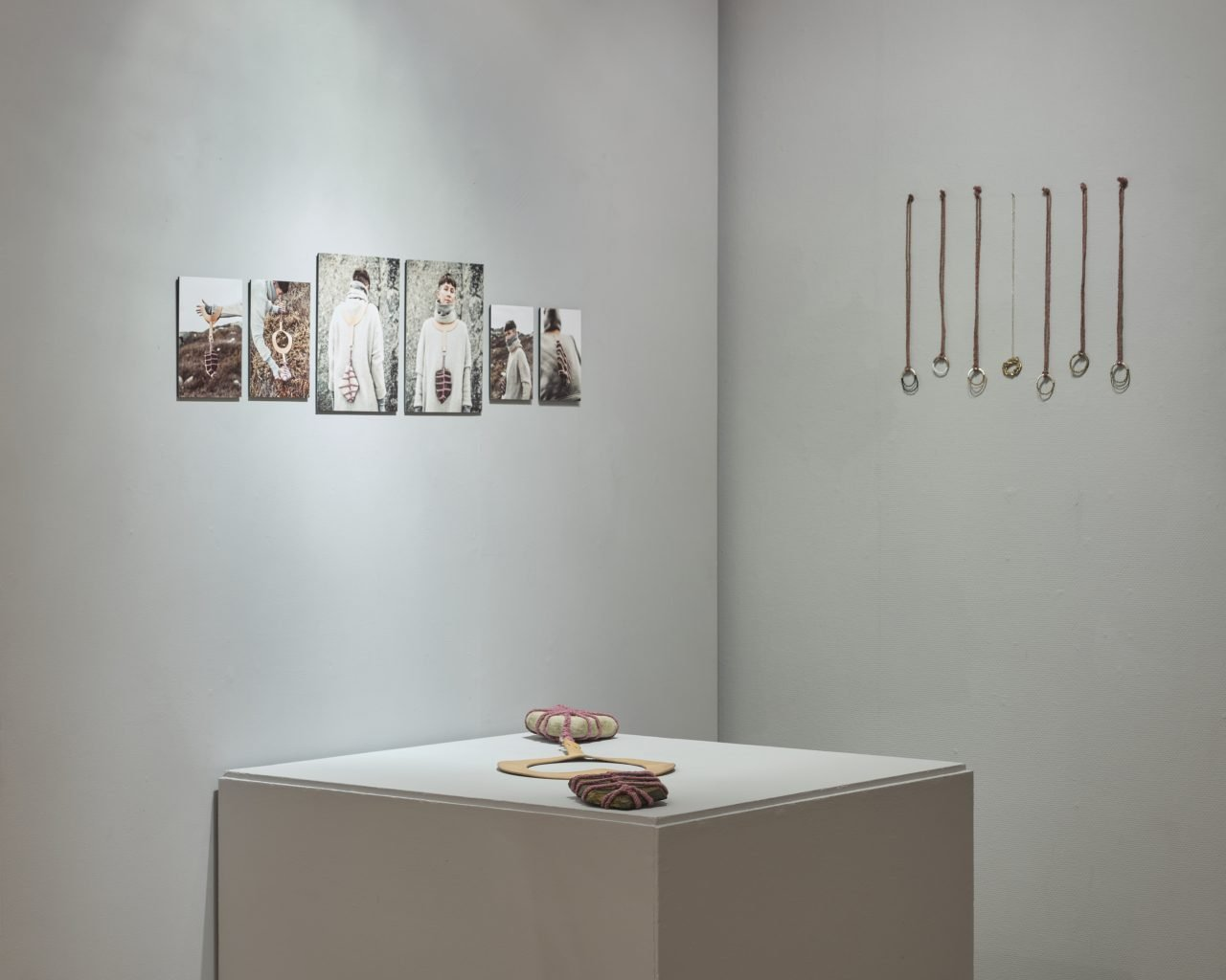 Oversized necklace made from leather, with stones wrapped in handmade rope on a plinth and small necklaces made of cast metal and handmade rope hung on the wall, with photographs of necklaces being worn
