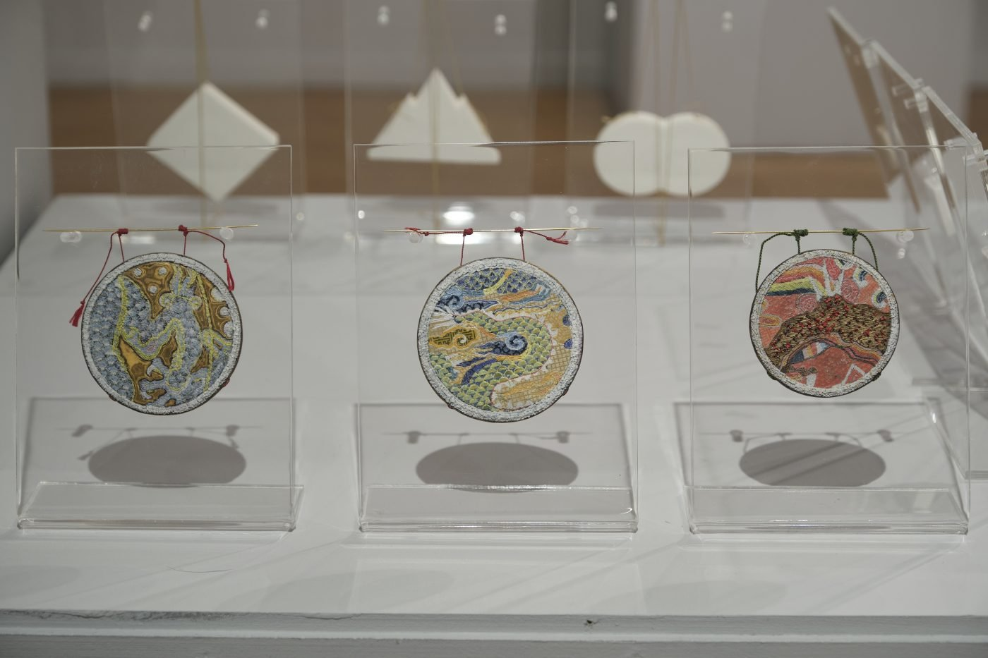 Three round brooches featuring dragon motifs, mounted on plastic display stands on a plinth