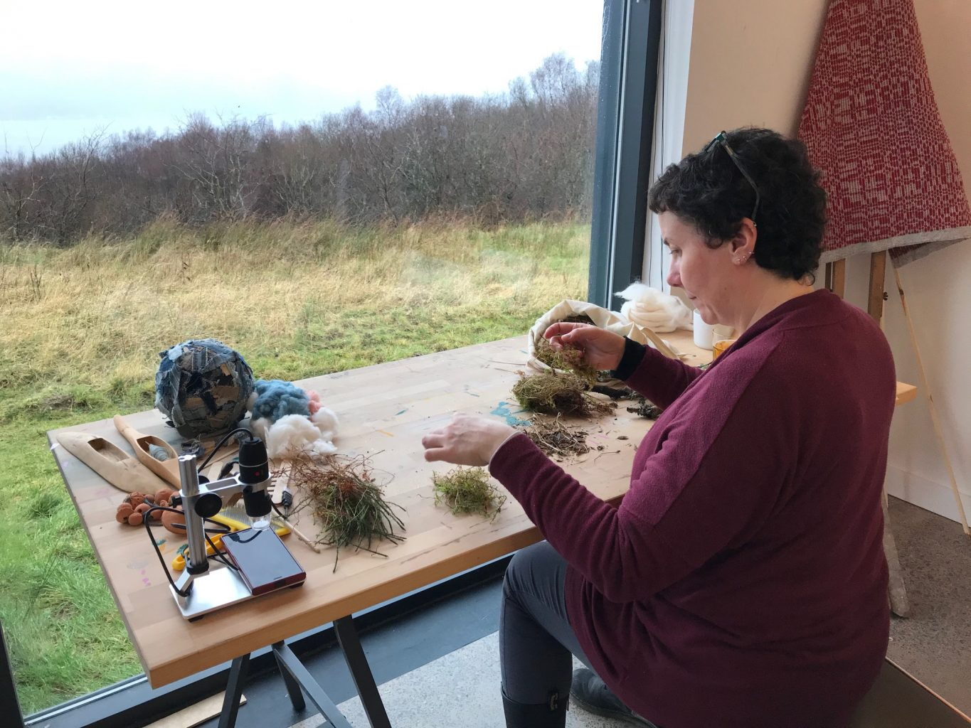 Woman seated a desk in a studio facing a floor to ceiling window sorting foraged natural material