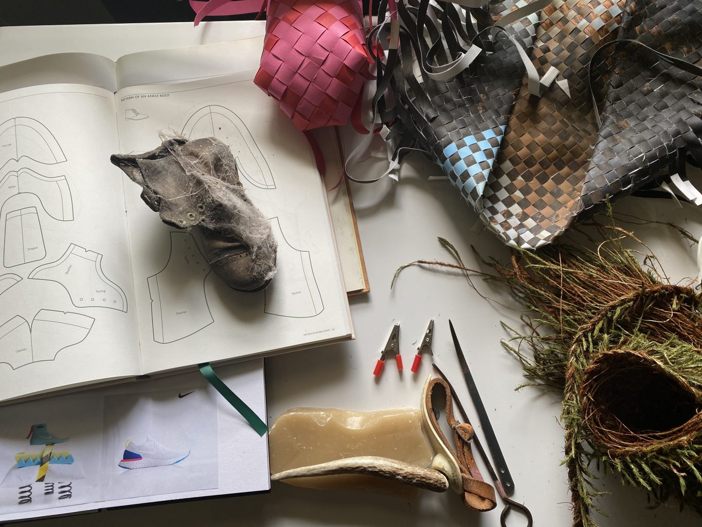 Images of trainers, open book with shoe pattern on the page, old children's shoe and samples of woven materials and baskets on a desk