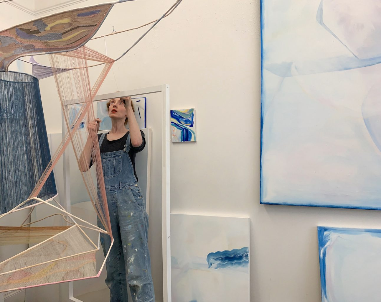 Artist stood working at an art work hanging from the studio ceiling, with artworks on the walls