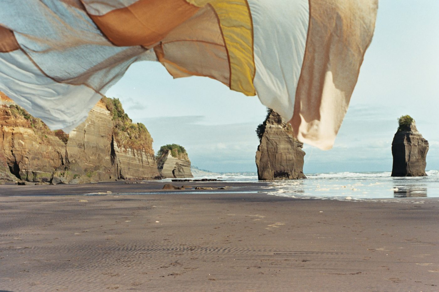 Textile artwork blowing in the wind on the beach, with the sea, cliffs and stacks in the distance