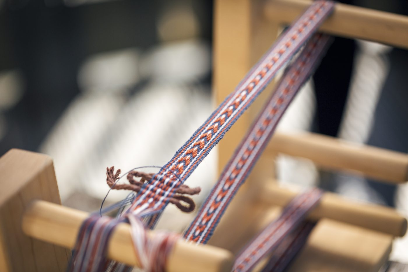 Thin band of blue, orange and white textile being woven on a loom