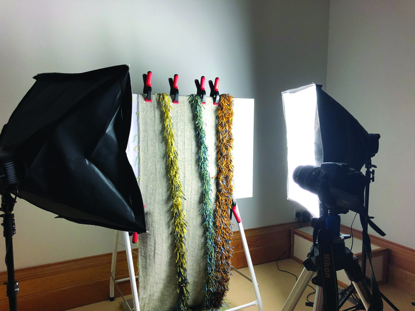 Woven cloth with linear fabric fringing hung upright on a board, lit with bright lights and a camera pointed at it
