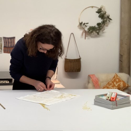 Female bent over a white topped table stitching on to fabric, with objects hanging on the wall behind