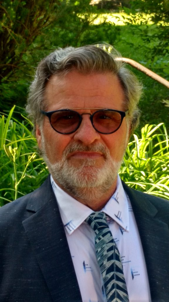Male with beard, wearing glasses, shirt, tie and jacket