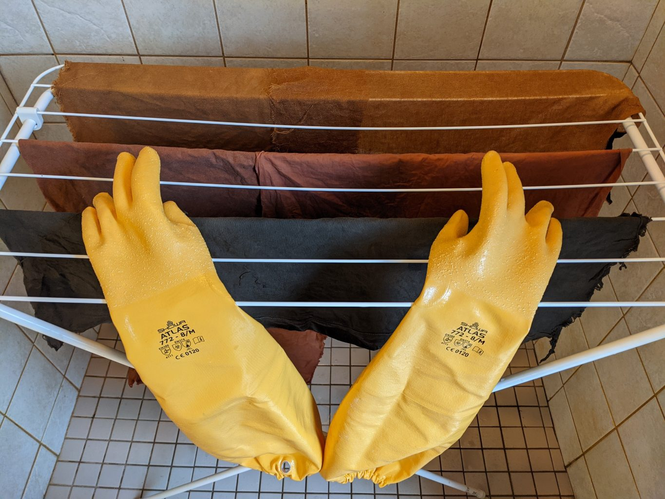 Clothes airer in a white tiled space, with three pieces of natural dyed fabric - dark blue, red and brown - hanging on it, with a large pair of yellow rubber gloves in the foreground