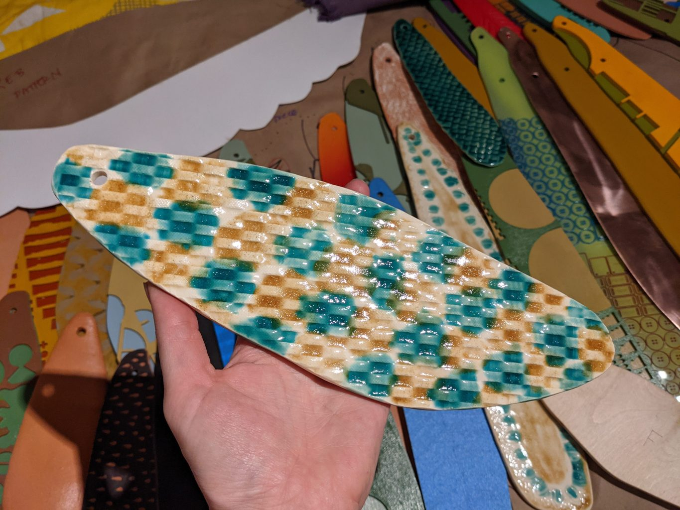Flat, feather shaped, ceramic piece with turquoise and deep orange glaze held in a hand above father shape cut outs of other materials