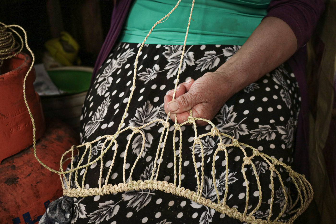 A woman's hands knotting a string like material into a traditional bag on her lap