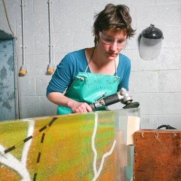 Female artist polishing the edge of a sheet of coloured glass in her studio