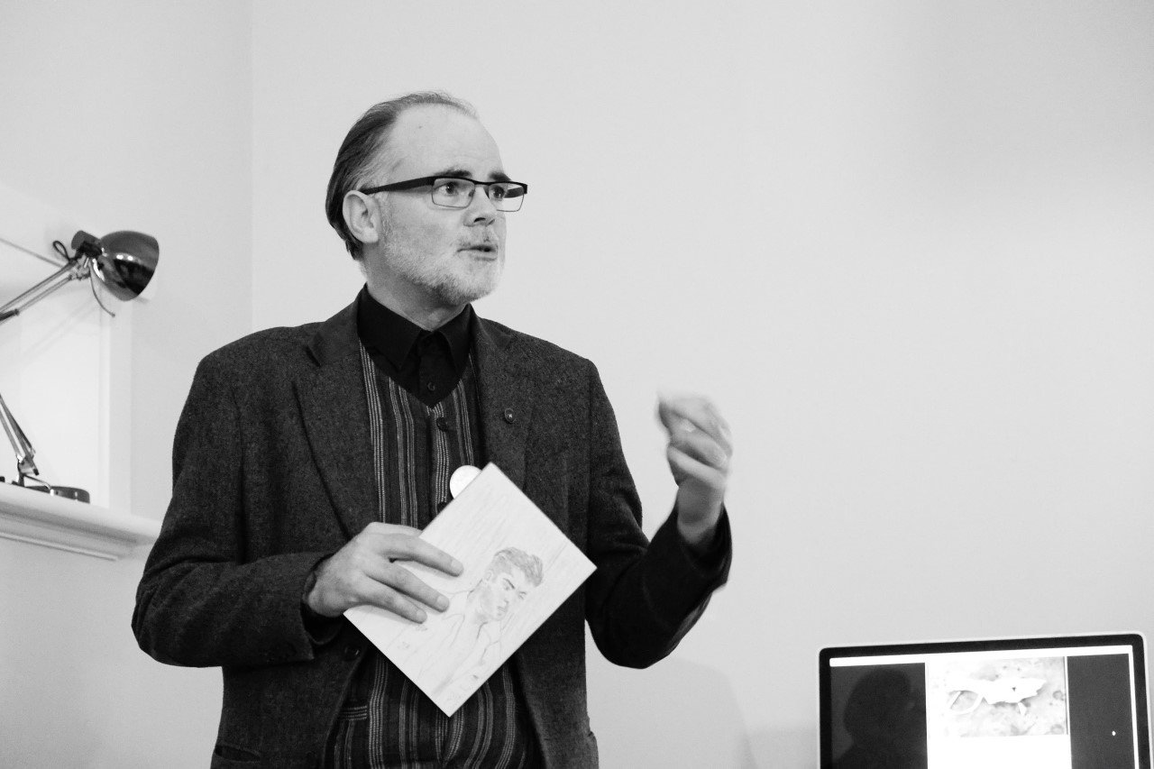 Standing man holding a magazine gesturing to an audience