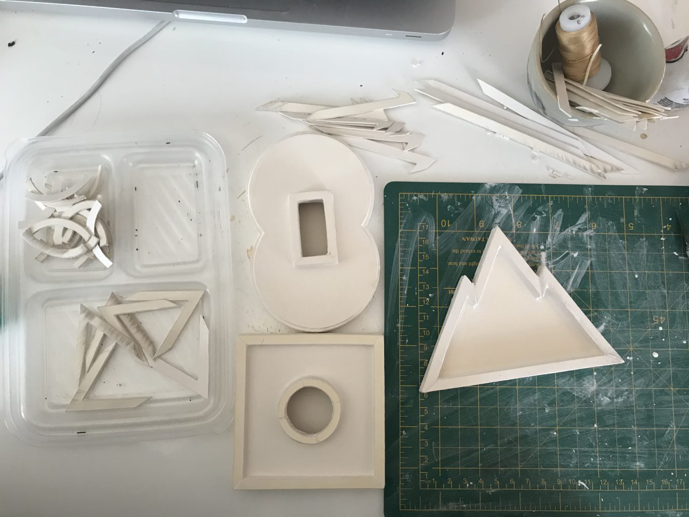 Geometric white pieces bring cut and constructed from clay on a table with a cutting mat