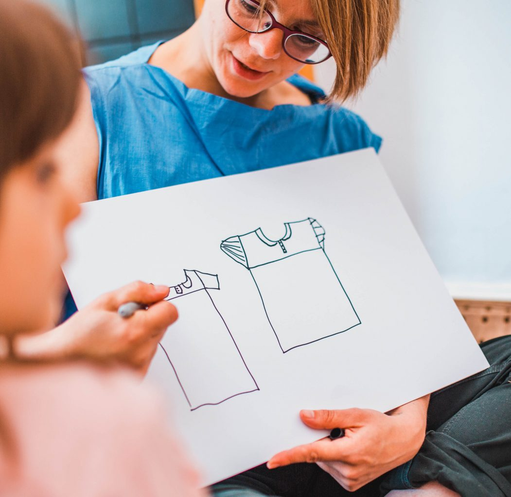 Female artist showing a line drawing of a short sleeved shirt to a young child