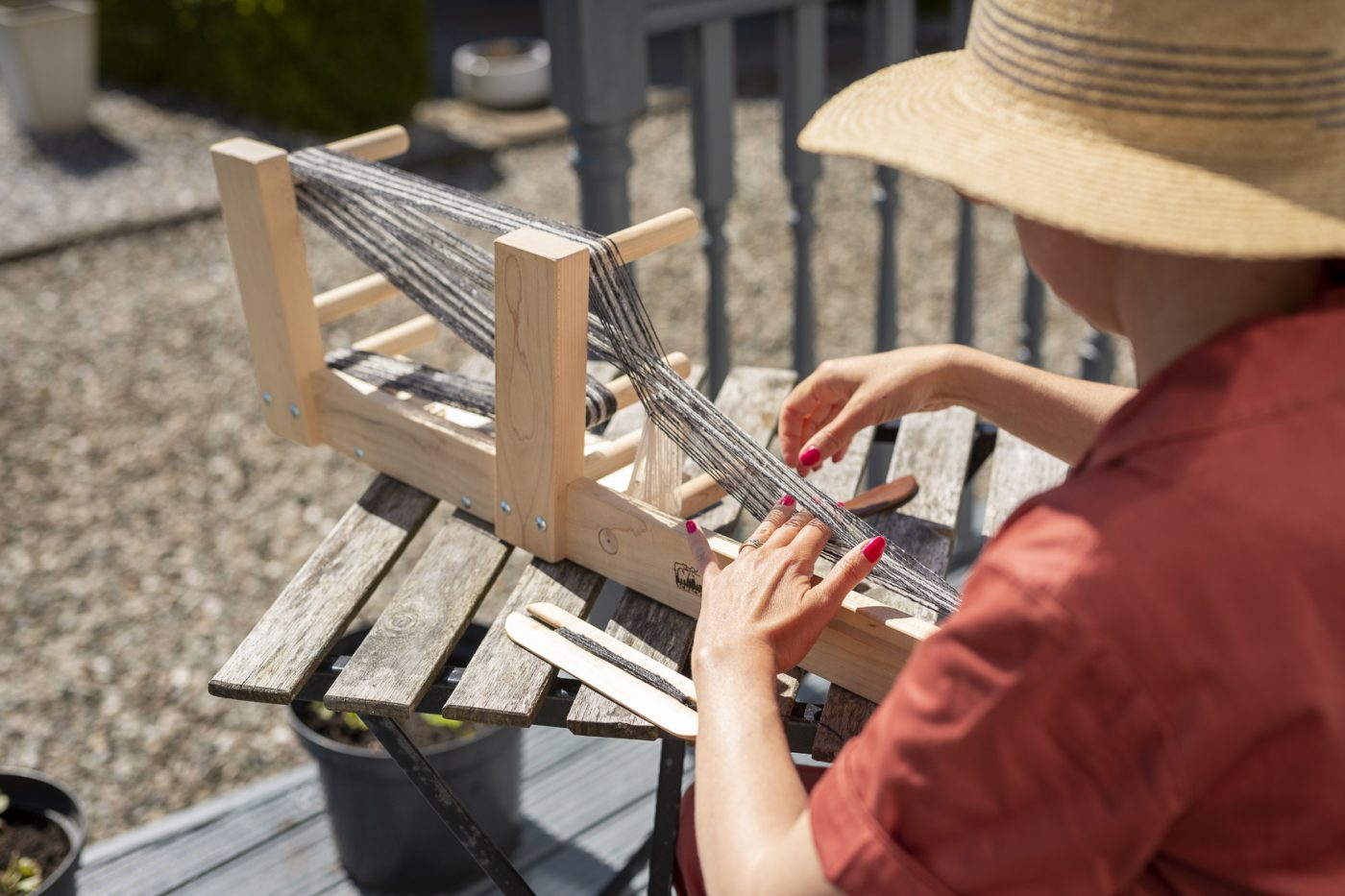 Female in a sun hat preparing a table top loom with grey and white thread ready to weave a thin band of textile