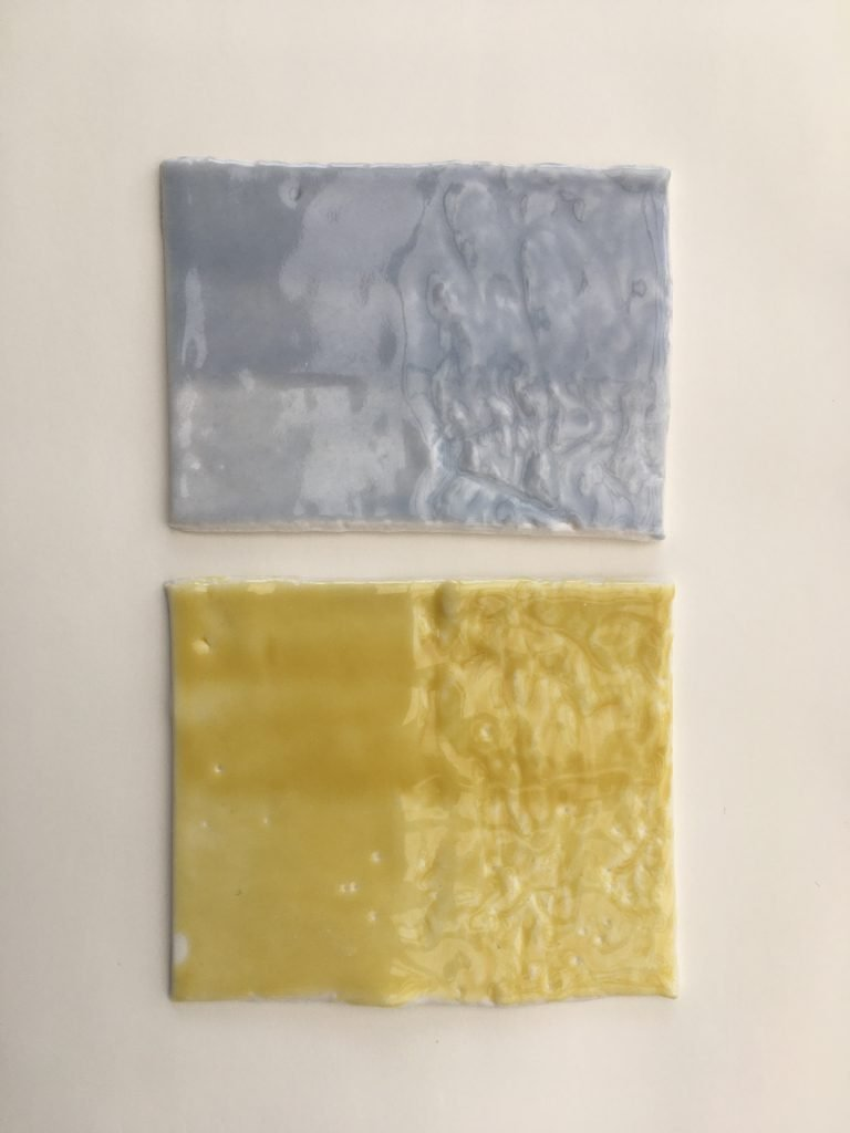 Two clay squares, the top one with a light grey glaze and the bottom one with a yellow glaze