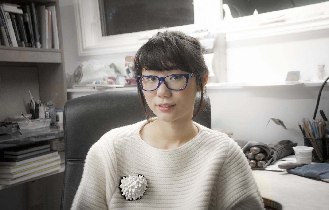 Seated artist wearing a large brooch on a knitted white sweater at a studio desk