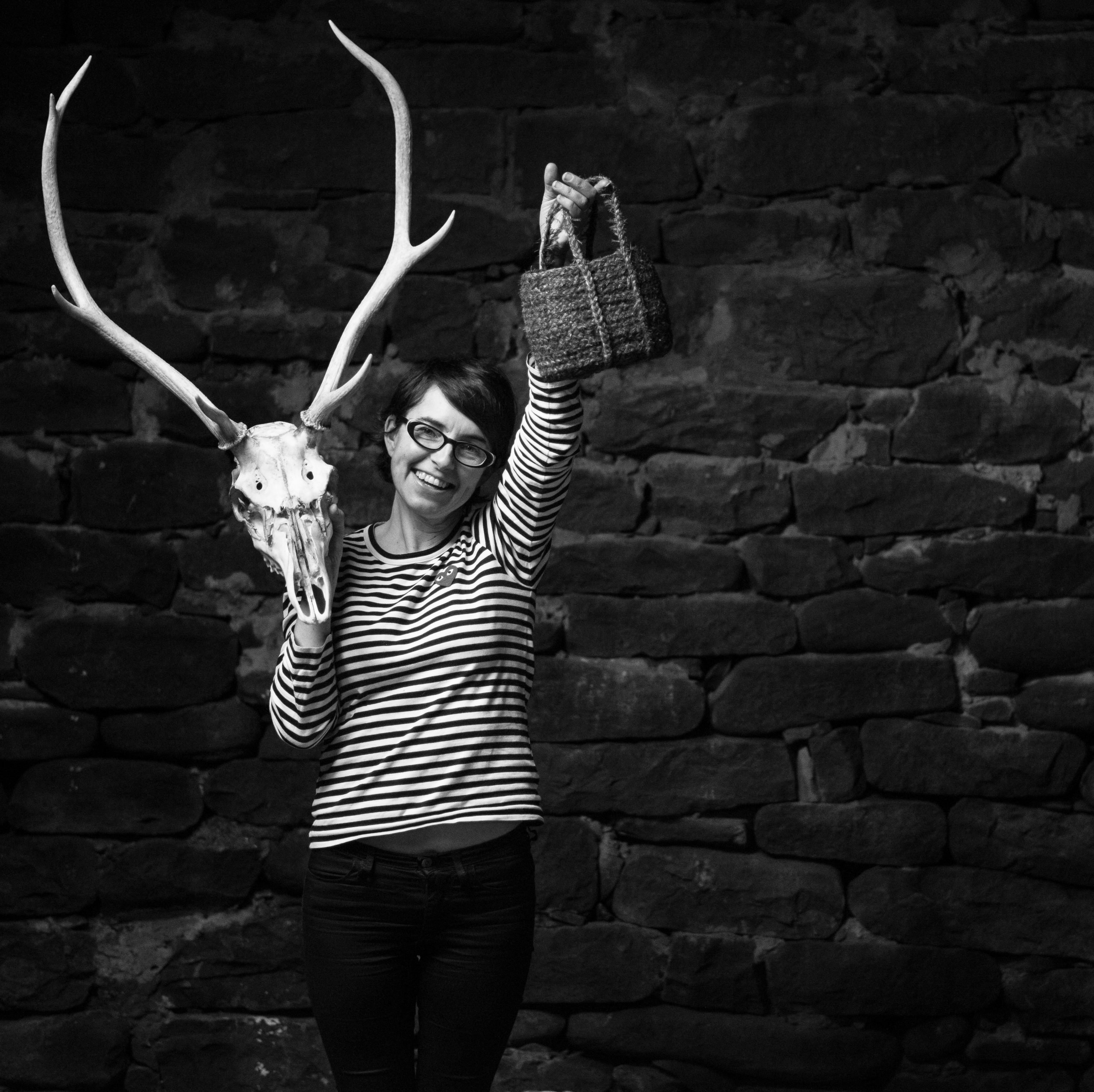 Standing female artist wearing a stripy long sleeved top holding aloft a hand woven small bag in her left hand an a skull with antlers in her right hand