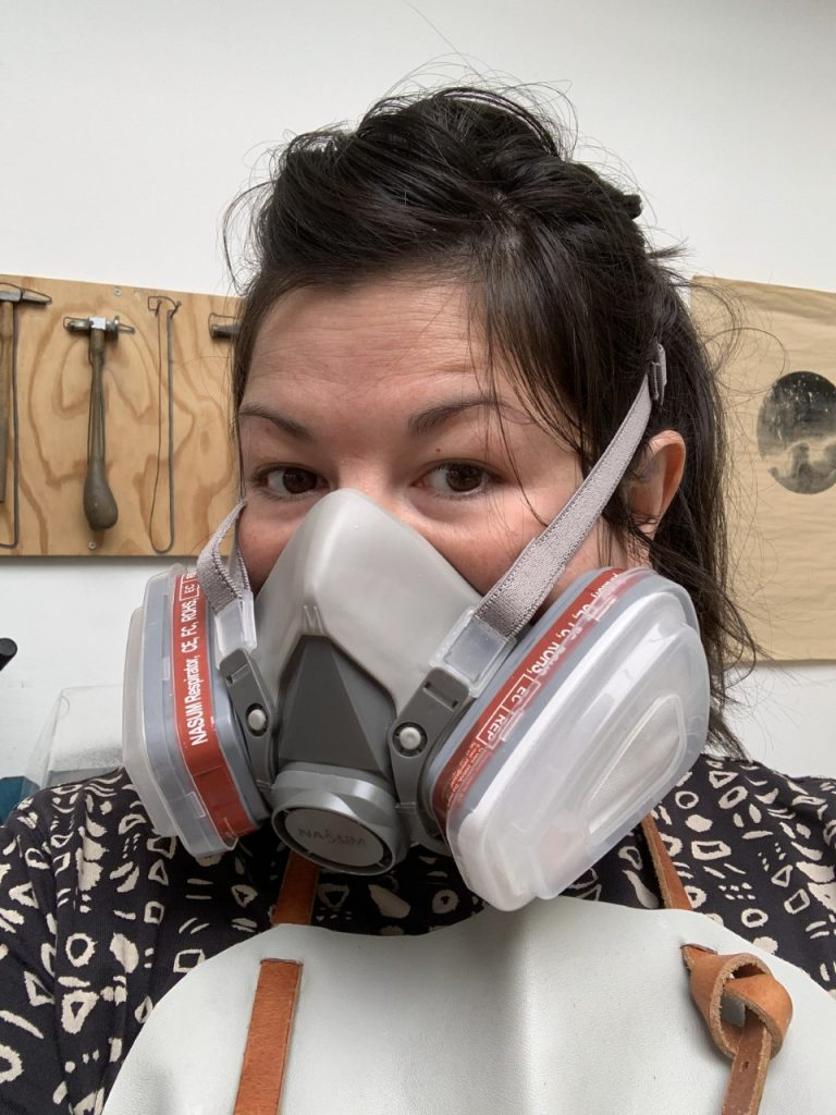 Female wearing a respirator mask and apron, stood in front of a wall with jewellery hammers on it