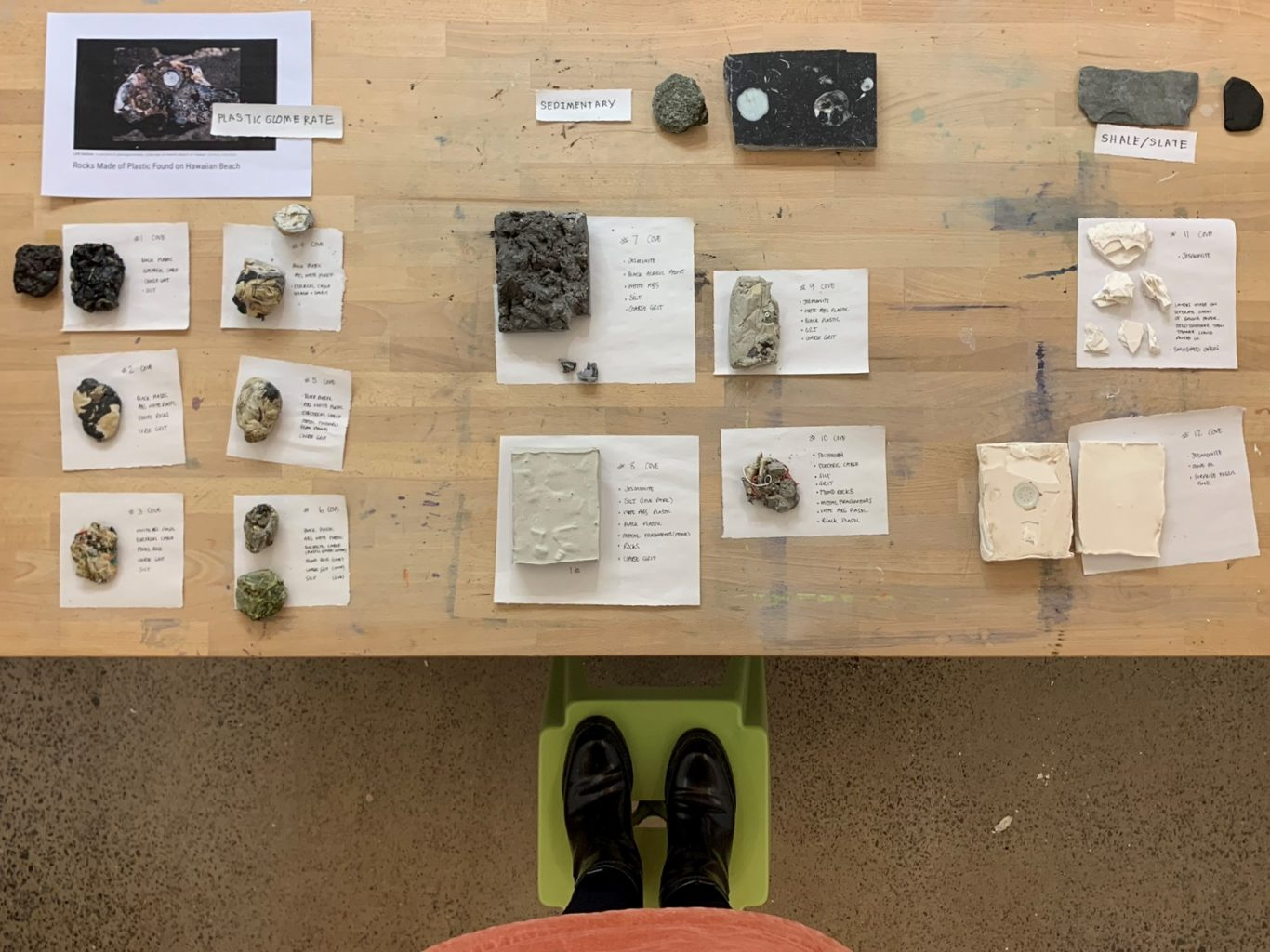 Wooden table top with samples of man made tock laid out on pieces of white paper which have notes about their creation