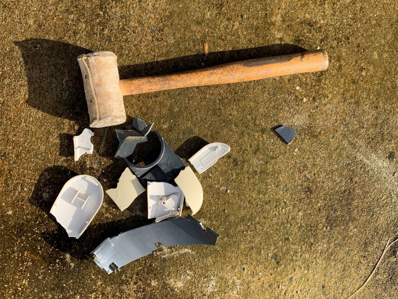 Broken pieces of formed white and grey plastic on the floor alongside a wooden mallet
