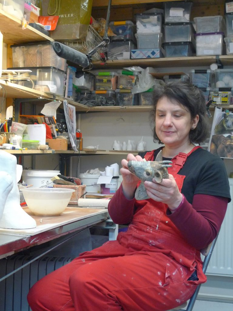 Female artist seated at a desk in her studio working on a ceramic animal head held in he hands