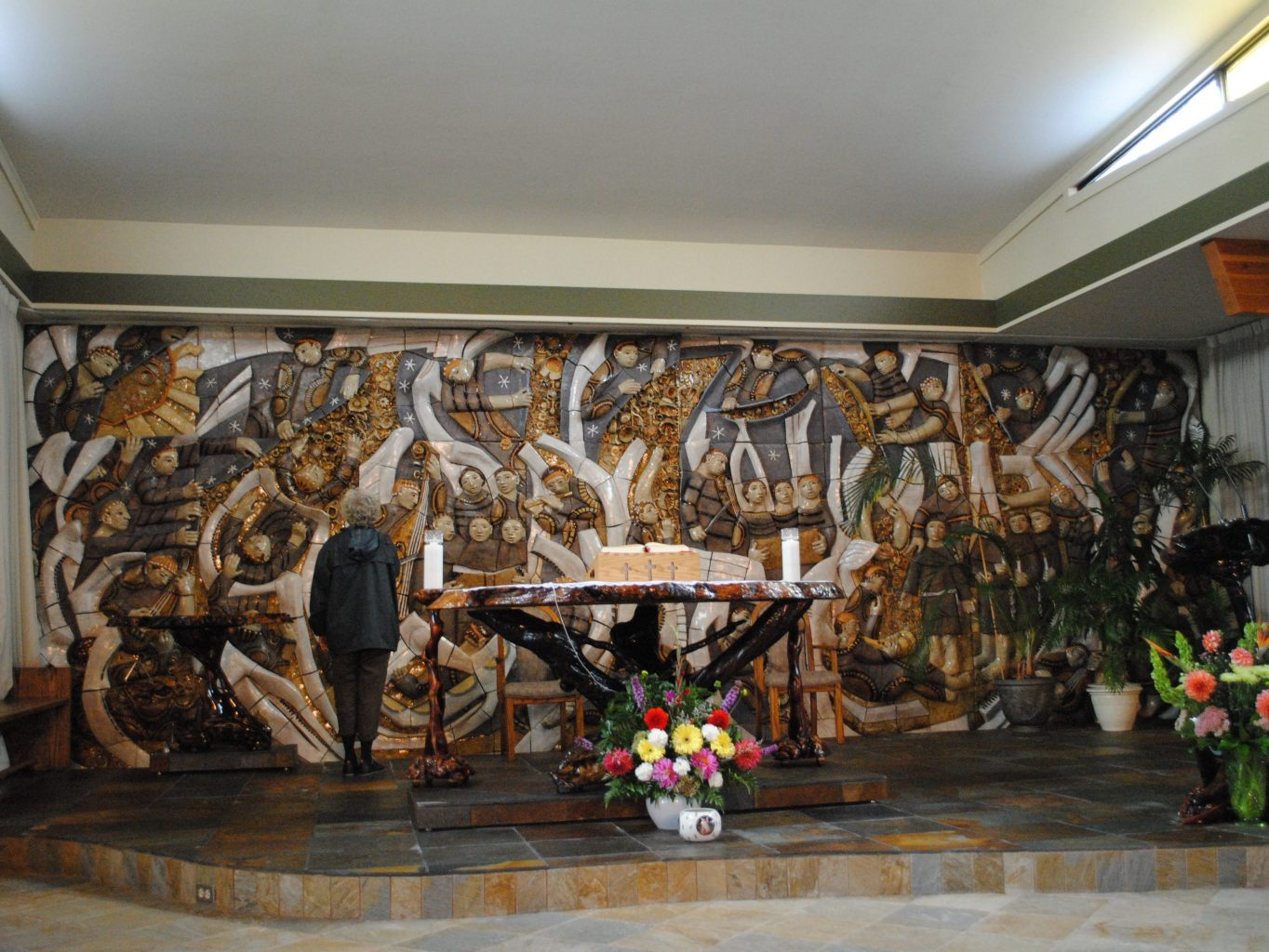 Female artist viewing her ceramic mural installed on a wall behind the altar of a church.