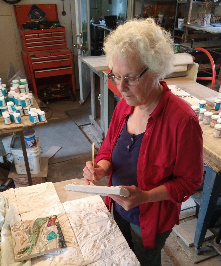 Female artist decorating ceramic panels in her studio