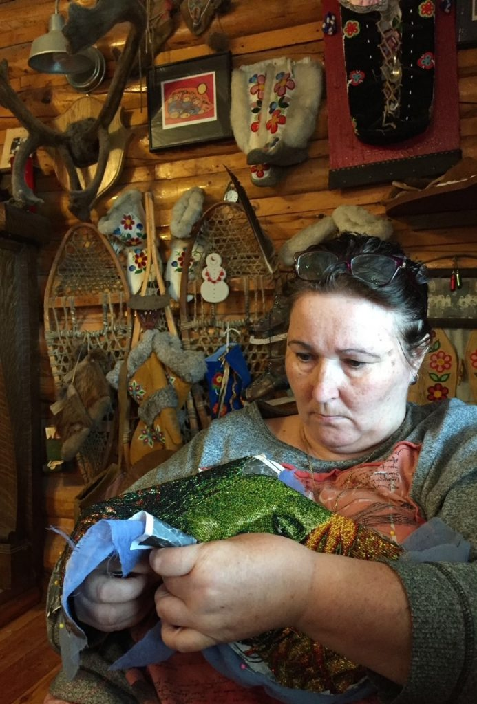Female artist stitching beads on to a textile artwork in her log cabin, with handmade objects hanging on the wall