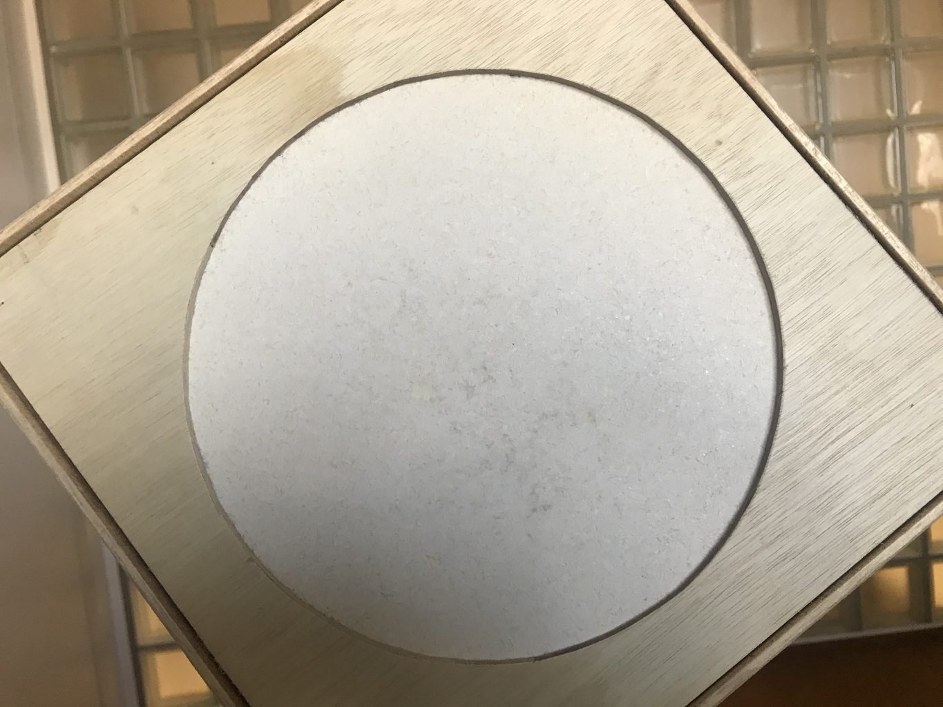 Square wooden frame with a circular opening, revealing white paper made with fish scales