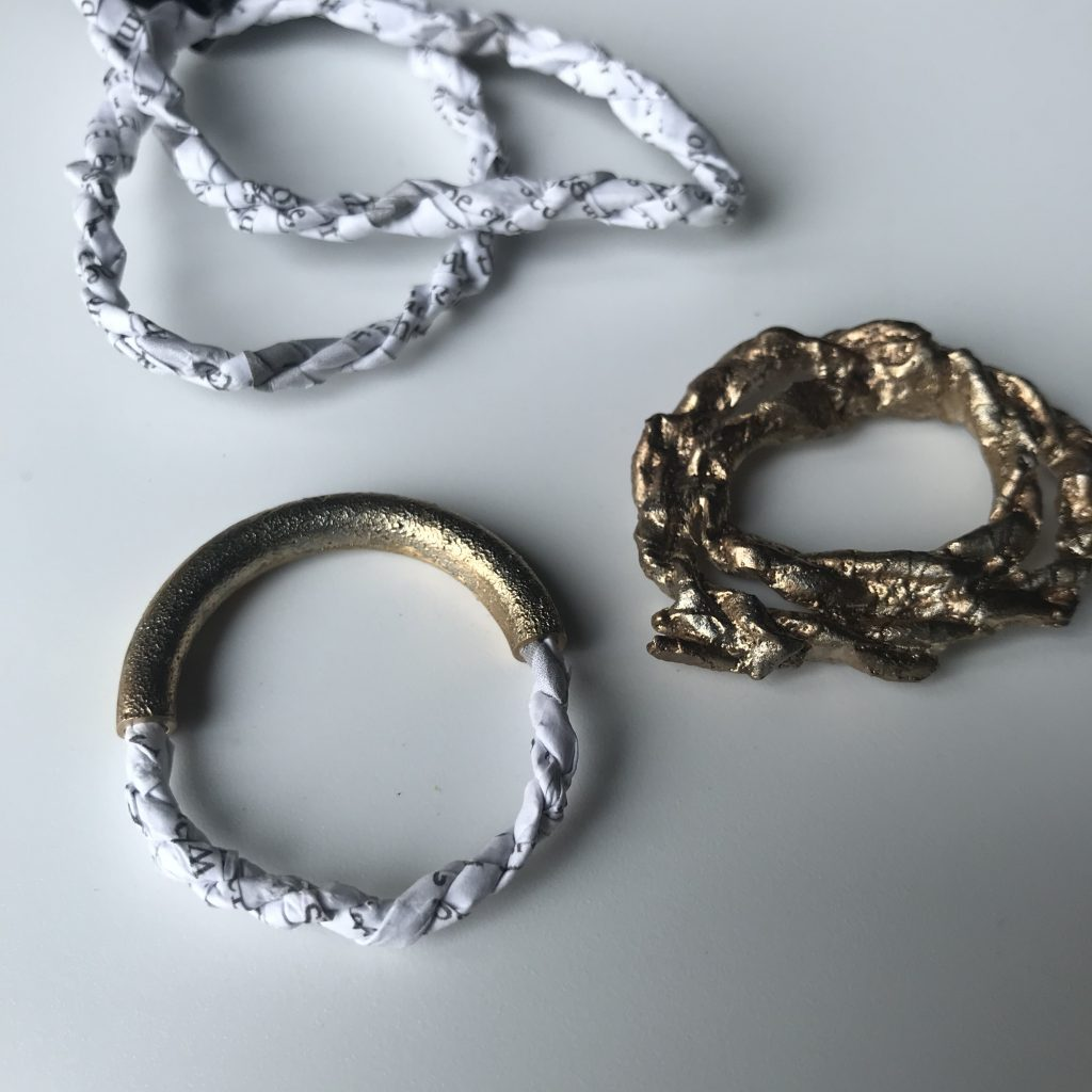 Small circular pieces of handmade paper rope cast with metal elements and in metal