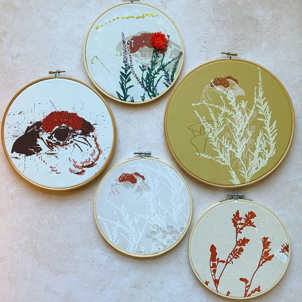 Five embroidery hoops, each stretched with white, cream or yellow fabric, some printed with flora and fauna, with differing types, style and amounts of hand embroidery in browns, yellow, red and orange