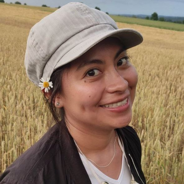 Female wearing a cap, standing in a field of wheat